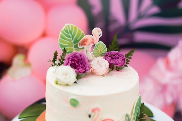 Pink cake with flamingos for the holiday. cake with a variety of decorations, palm leaves and fresh flowers