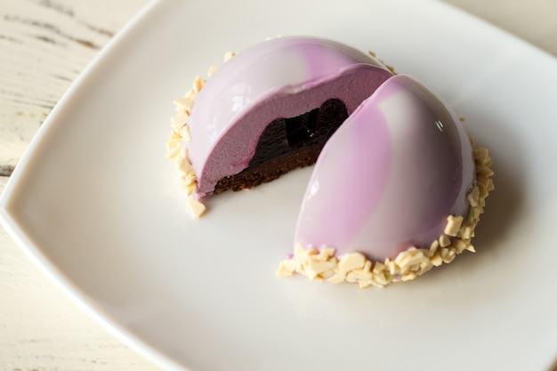 Pink cake with glaze. dessert with dark filling. blueberry jelly and mousse. snack at birthday party.