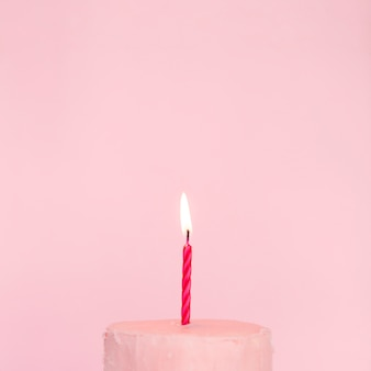 Pink cake with lit candle