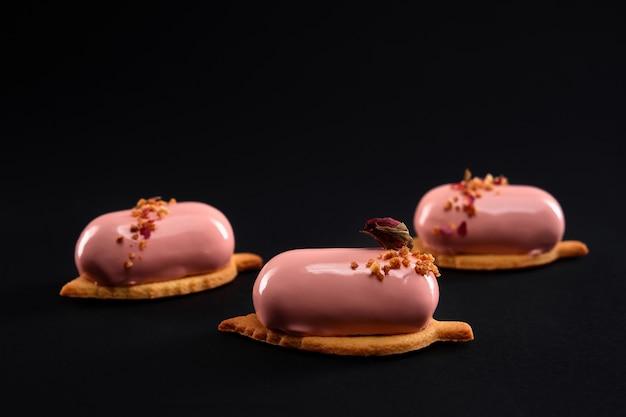 Розовые торты, украшенные орехами и сухим цветком розы изолированы