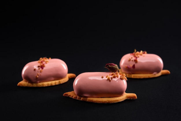 Pink cakes decorated with nuts and dry rose flower isolated