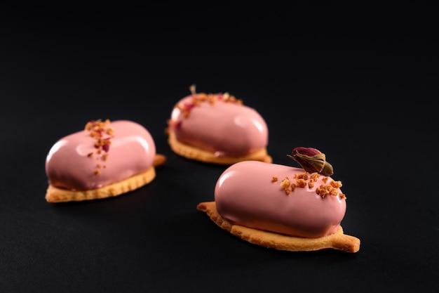 Розовые торты с глазированной гладкой поверхностью, изолированные на черном.