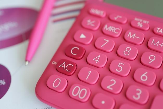 ボールペンのクローズアップの近くのグラフでドキュメントに横たわっているピンクの電卓