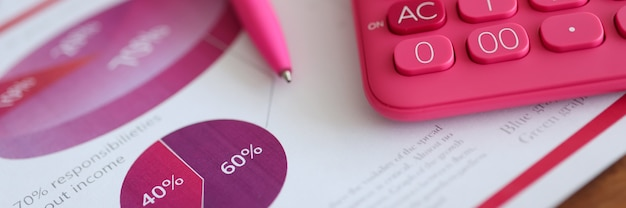Pink calculator and pen lying on document with graph closeup