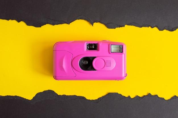 色の背景にピンクのカメラ。夏の静物。最小限