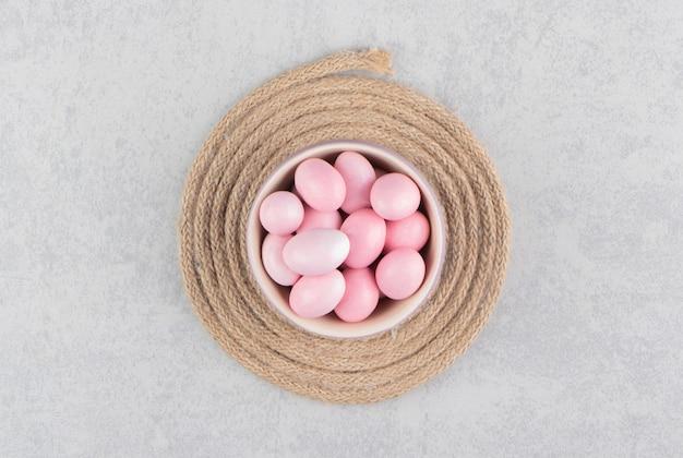 大理石の表面のトリベットのカップにピンクのキャンディー
