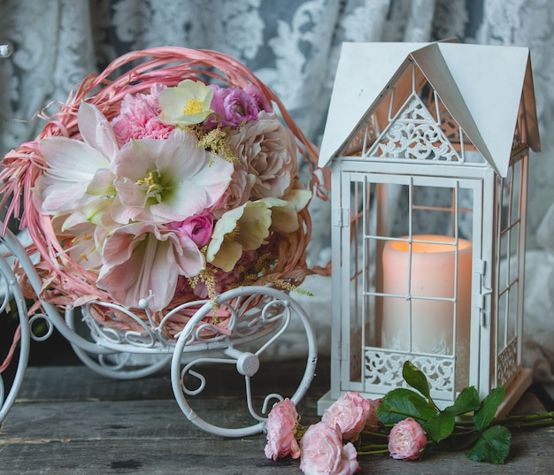 Pink candle in a fake cage, small wreath of flowers.