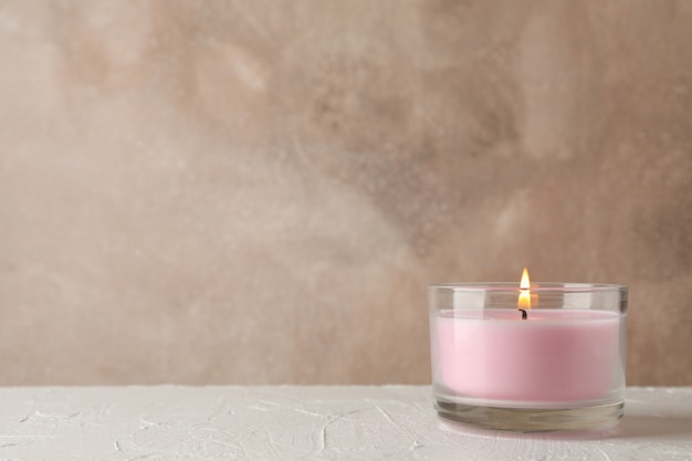 Pink candle in glass jar on white table