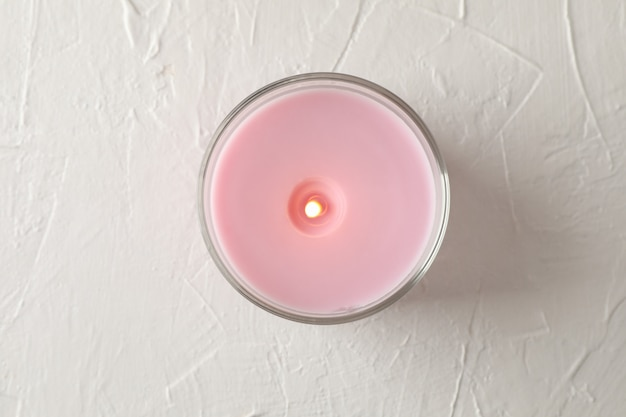 Pink candle in glass jar on white, top view