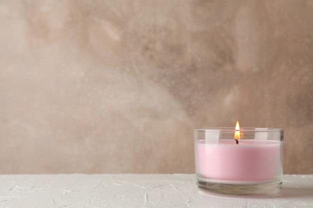 흰색 테이블에 유리 용기에 분홍색 촛불