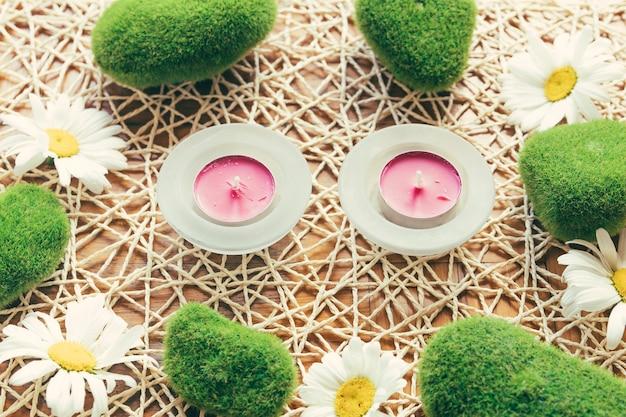 분홍색 촛불과 이끼 낀 돌