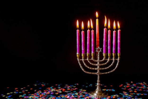 Розовые свечи на меноре и конфетти на черном фоне. еврейский праздник символ хануки.