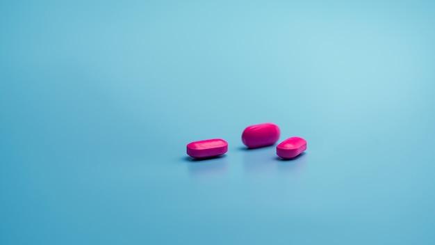 青い背景の上のピンクのカプセルの丸薬。製薬業界。健康と医学。