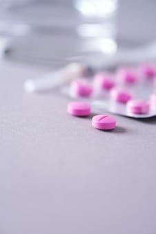Розовая капсула, таблетки, витамины на сером фоне. копировать пространство куча лекарств, лечение простуды. лечение женской болезни.