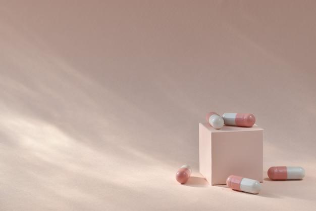Розовые капсулы разбросаны по кубу с местом для текста