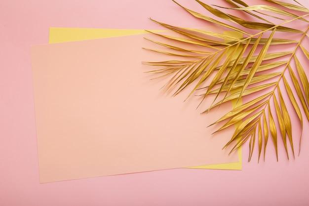 황금 야자수 잎으로 만든 프레임의 텍스트를 위한 분홍색 카드 복사 공간. 열 대 야자수는 분홍색 배경에 둡니다. 금박을 칠했습니다. 여름 꽃 배경입니다.