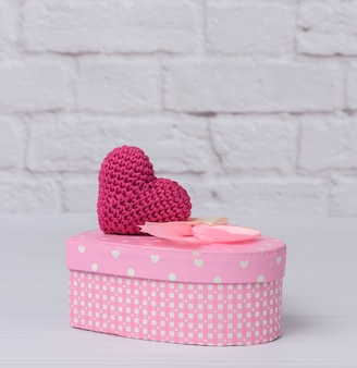 Pink cardboard box in the shape of a heart on a white background. festive background