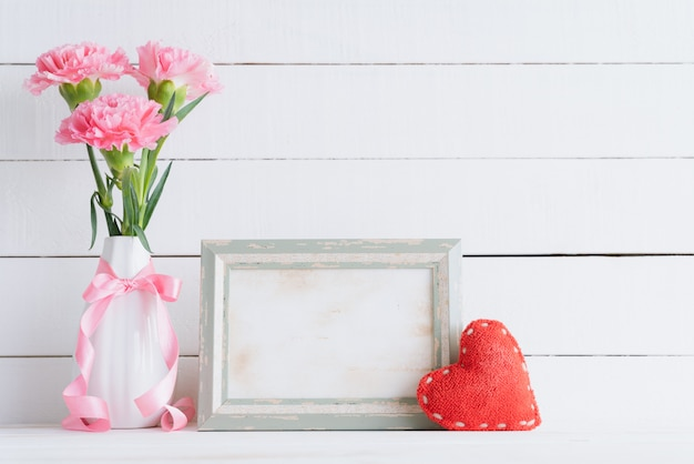 Pink carnation flower in vase with old vintage picture frame and red heart