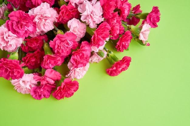 녹색 벽에 핑크 카네이션 꽃 꽃다발입니다.