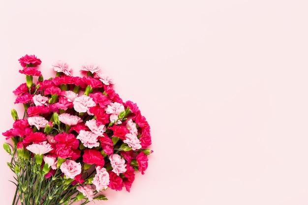 ピンクの背景にピンクのカーネーションの花の花束。母の日、バレンタインデー、誕生日