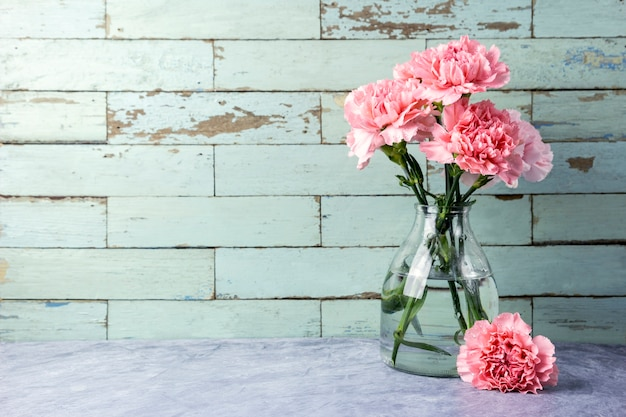 Pink carnation flowers in glass bottle with copy space