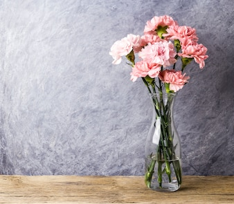 Pink carnation flowers in clear bottle with copy space