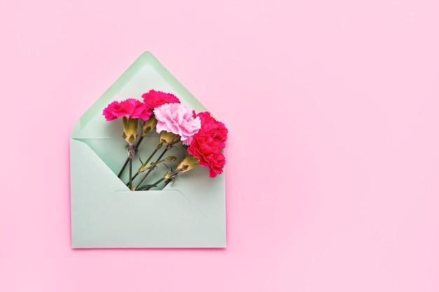 핑크 파스텔 벽에 녹색 봉투에 핑크 카네이션 꽃.