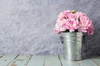 Pink carnation flowers in zinc bucket on old wood