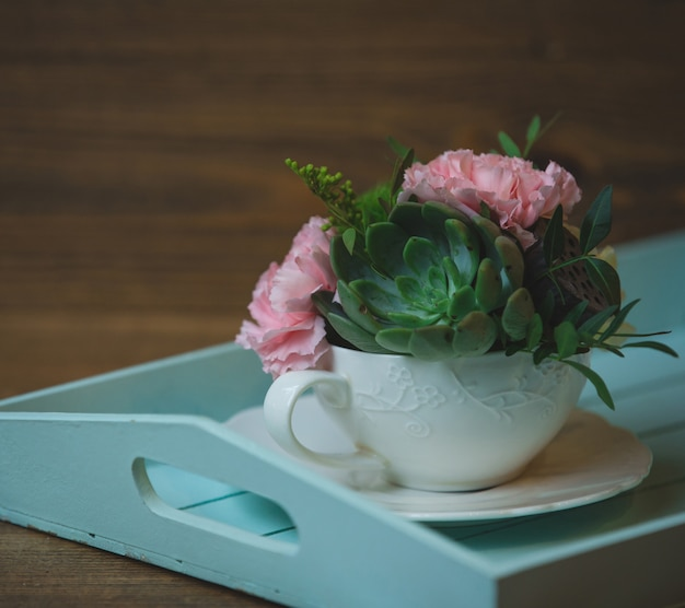 Розовые гвоздики и цветы кактуса внутри чашки
