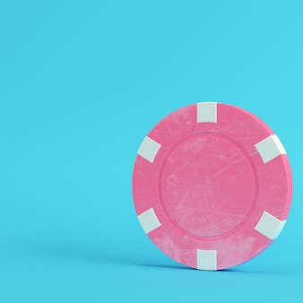 Pink casino chip on bright blue background