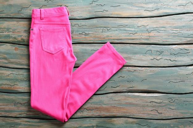 핑크 캐주얼 팬츠. 나무 배경에 접힌 바지입니다. 녹색 선반에 여자의 바지입니다. 경매장에서 구입한 옷.