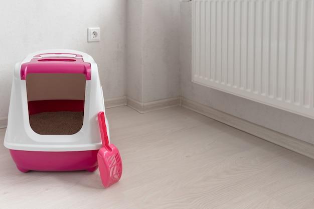 部屋にスクープが付いているピンクの猫のトイレ