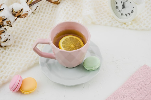 Pink ceramic cup with lemon tea and macaroons on white backdrop