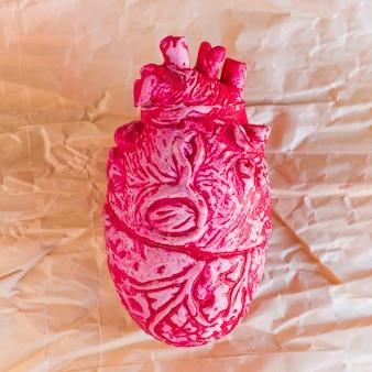 Розовое керамическое человеческое сердце на бумаге