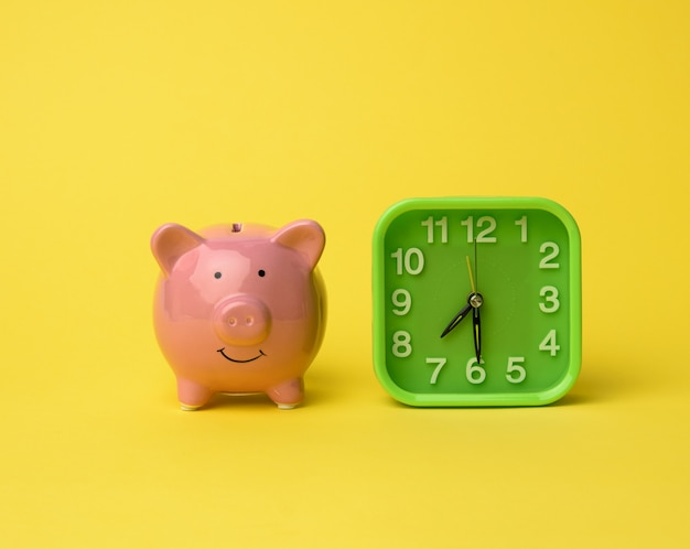 핑크 세라믹 돼지 저금통과 노란색 벽에 사각 녹색 알람 시계를 닫습니다.