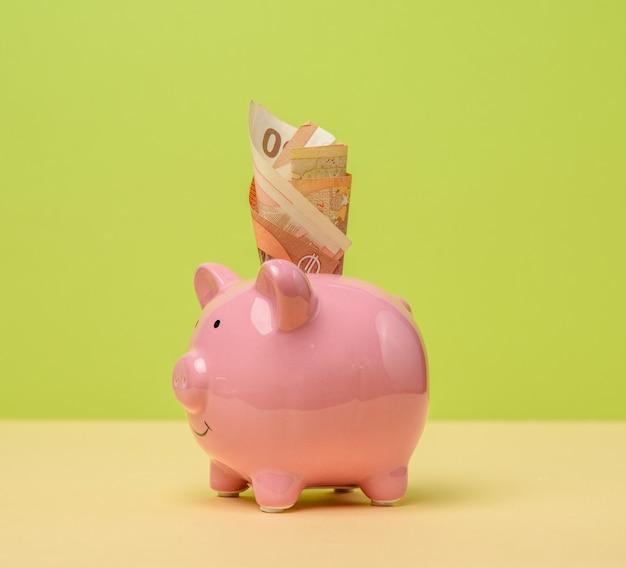 Розовая керамическая копилка и заправленный пучок евро, концепция сбережений и инвестиций, крупный план