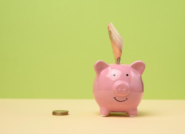 Розовая керамическая копилка и заправленный пучок евро, концепция сбережений и инвестиций, копировальное пространство