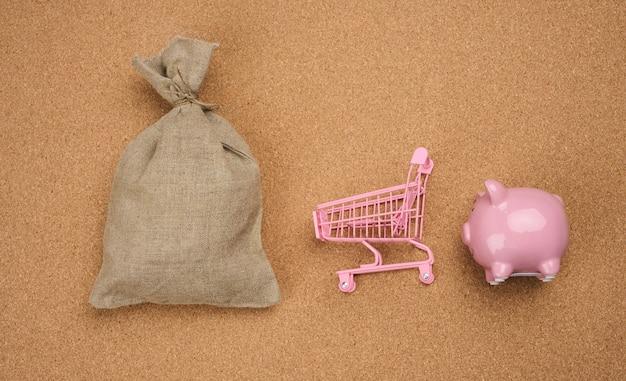 ピンクのセラミック貯金箱、ミニチュアショッピングカート、茶色の背景にフルキャンバスバッグ、上面図。