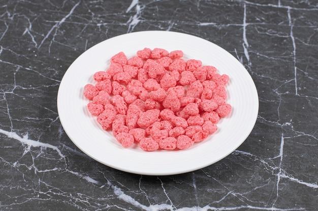 하얀 접시에 핑크 시리얼 조각입니다.
