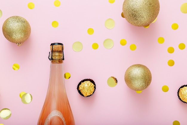 Розовая бутылка шампанского с конфетти пробковой крышкой и рождественские шары золотые рождественские украшения на розовом фоне. плоская планировка крупным планом.