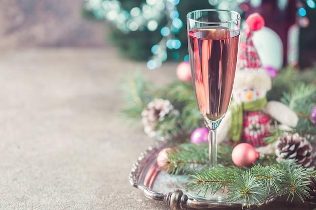 ガラスとクリスマスの装飾のピンクのシャンパン