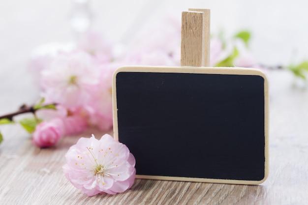 黒いチョークボードにコピースペースを持つピンクの桜の花