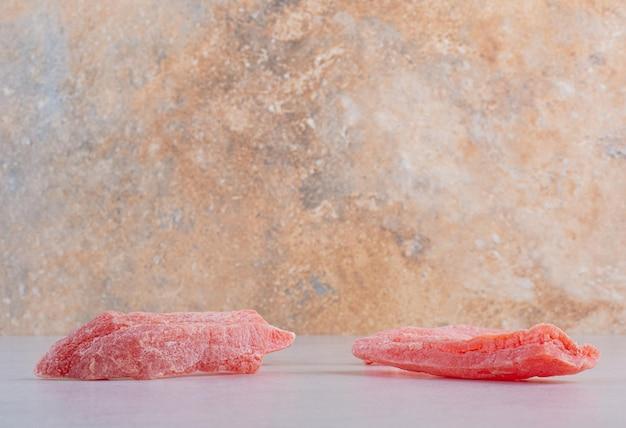 Bastoncini di marmellata di ciliegie rosa su fondo di cemento.