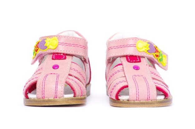 白で隔離のピンクの子供のサンダル