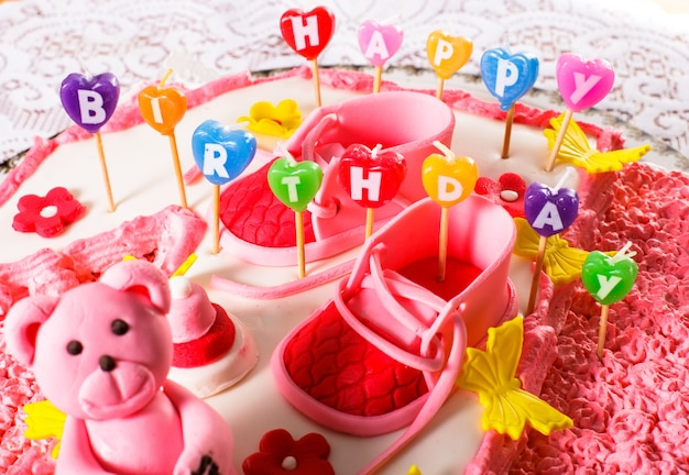 A pink children's birthday cake with happy birthday candles