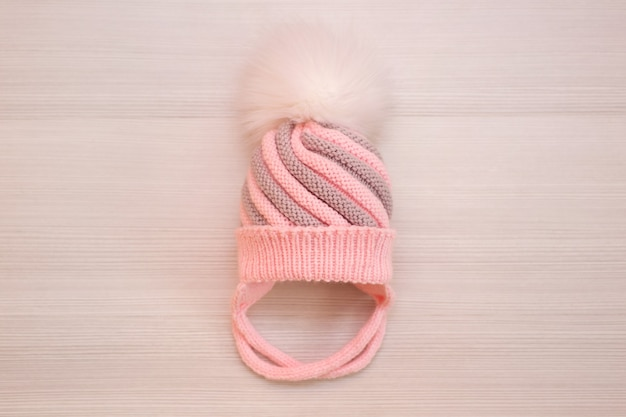Pink children's knitted wool hat with a pompom, on a white background