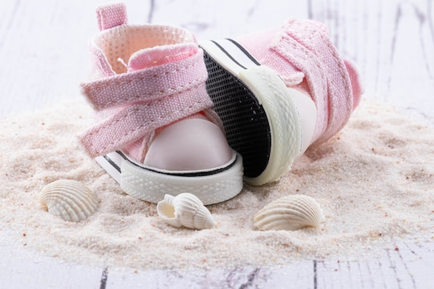 Pink children's shoes on white sand, seashells