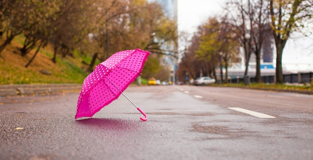 Pink children's umbrella on the wet asphalt outdoors