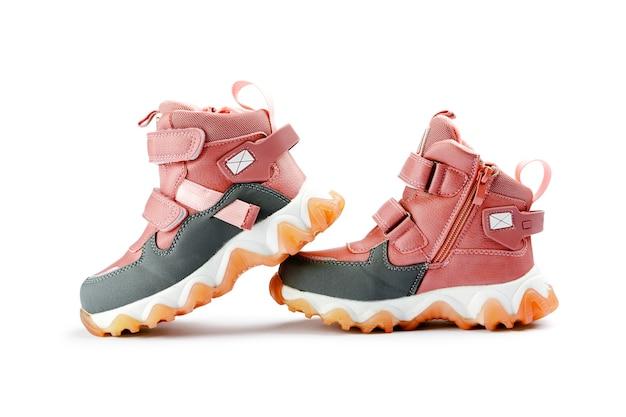 白い背景の上のピンクの子供たちの冬のブーツ。秋または冬のファッション。ベビーシューズ
