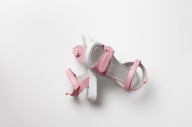 광택이 있는 가죽으로 만든 핑크색 아동용 샌들, 벨크로 잠금장치가 있는 평평한 흰색 밑창이 흰색 배경에 분리되어 있습니다.